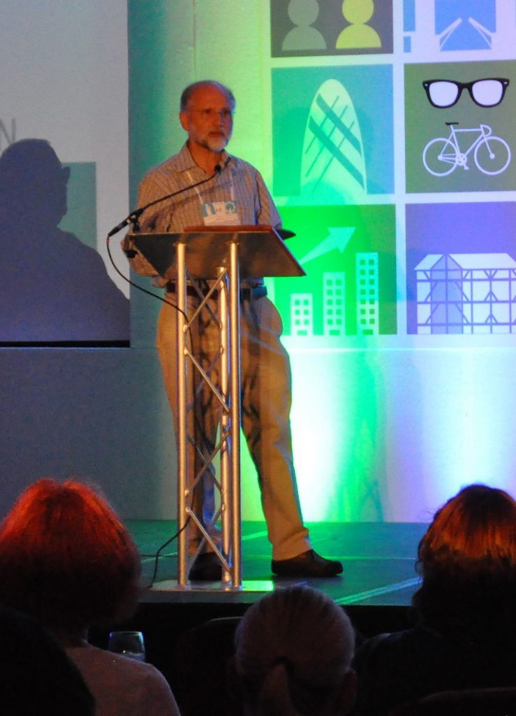 Photo of Nigel Bevan standing at a lectern and addressing the audience.