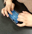 photo of hands and device of participant 1, group E-1 using the device.
