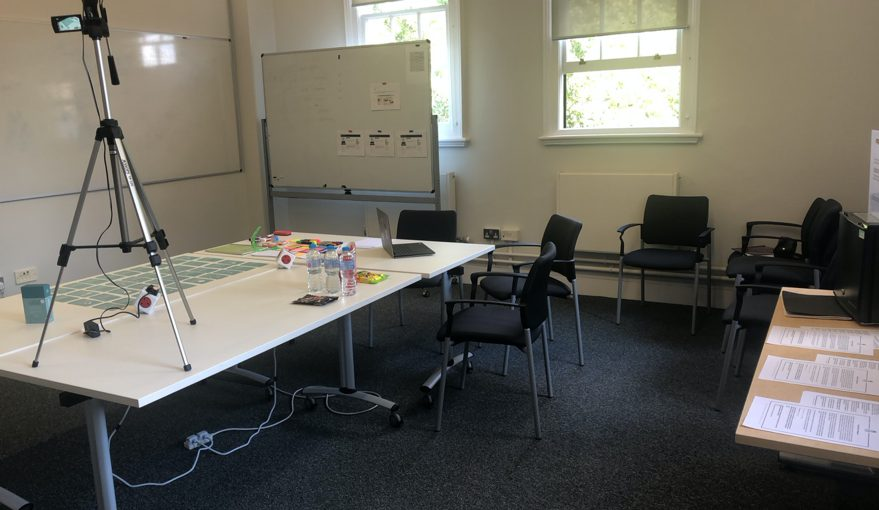 Photo of the with-cards sessions setting. The cards were spread out on the table, laptop with internet connection, whiteboard, papers, pens and sharpies, camera.